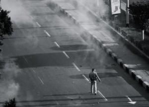 Ein Demonstrant wird auf einer Straße in Kairo von Tränengasschwaden umgeben - Copyright: Mariam Soliman