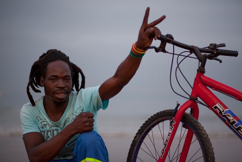"Sam Chiota: ""It was long time… I was just going… my father used to buy me bikes… so even me, I enjoy biking… even training… chase …chases …okay, I used to ride a bike, another time I rode a bike from Johannesburg to the Free State. Then from there, I got a lift up to Durban. Then here, always, I'm always riding bike. Every day. It just make me strong. That's why I like it. I was born in Zimbabwe. I didn't know how far is Durban was. I was thinking maybe I can ride up to Durban. I was feeling to ride up to Durban. And when I see that there is a long way, I take a lift… I was just riding but if I feel like I am tired really, I can just park my bicycle at the side of the bush and I can just eat my food because I buy my food on the way. Then I eat my food, start riding again. I've been here in Durban for one year, almost eighteen months. I'm doing dreadlocking. I am very busy on weekends because people will take my numbers and most of the time they go to work so we are free on the weekend to make the dreadlock. I use only a needle. I don't put wool. I don't even put the medicine. I use a needle called a crochet. So it's just the hair. The hair comes together… I used to be another time three months in Cape Town… I was also busy making dreadlocks. There in Cape Town are too many Rastas so I had no clients. The price is according to how long the hair is but the price is starting from R250 for small hair, to R350, R400… it's according to how long is the hair. If someone have got the dreadlock, I can take the dreadlock together to make it strong. If you want to take three or four together to make it strong. Dreadlocks mean something special to me - some they are doing it as a fashion but it means something special to Rasta people, because Rasta people, they believe that you mustn't cut your hair. You must just leave it as it is because it's natural, the hair. So Rasta people just like it as it is. Mostly they don't like to kill something … so it's a belief… especially me, I keep my hair. Me, I am a Rasta"""