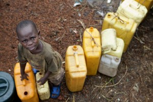 A young boy waits to fill his containers at a water distribution area, Copyright: UN Photo by Sylvain Liechti