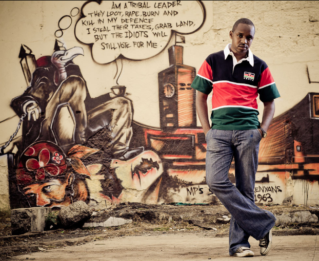 Political activist and graffiti artist Boniface Mwangi poses in front of a mural near Nairobi's City Market that depicts corruption in Kenya. © Allan Gichigi