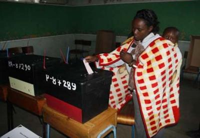 A woman casts her vote with her child at Kenya's 2007 elections. © DEMOSH