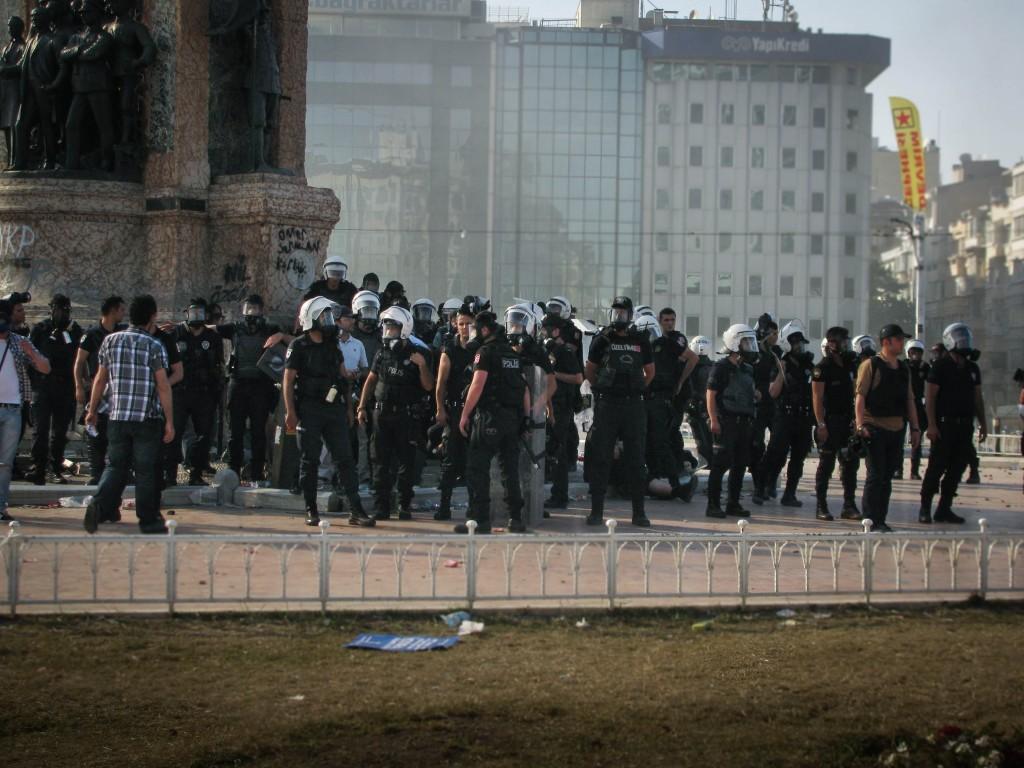 Polizisten am Atatürk-Denkmahl auf dem Taksim-Platz schirmen eine Festnahme gegen Kameras ab. © Almut Dieden