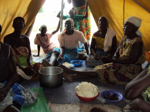 Women about to have a communal meal inside a tent (Photo by Deogracias Benjamin Kalima)